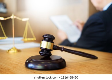 lawyer judge reading documents at desk in courtroom working on wooden desk background. gavel  golden Weight. and soundblock of justice