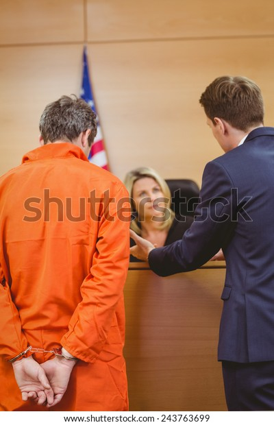 Lawyer and judge speaking next to the criminal in handcuffs in the court room
