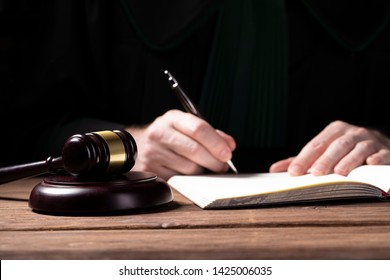 A lawyer looking at the penal code with magnifying glass - searching for the right sentence
