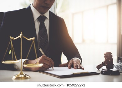Lawyer in the office with brass scale and writing in contract on wooden table. Justice and law concept.