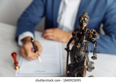 Lawyer office. Statue of Justice with scales close-up and lawyer sighning a document. Legal law, advice and justice concept