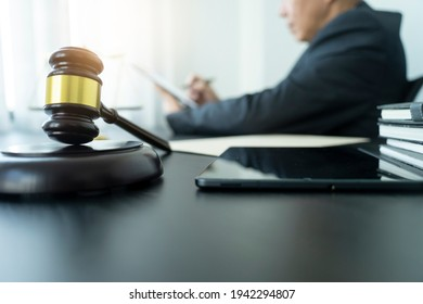 The lawyer is reviewing the draft of legal documents or contracts for clients near the tablet. - Shutterstock ID 1942294807