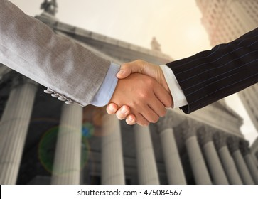 Lawyer shaking hands with businessman with court background. Concept of legal services, legal advice, law.