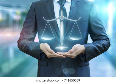 Lawyer showing the scales of justice on a blurred background.