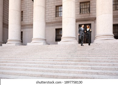 A lawyer  and their client  or business people walk down the staircase of a courthouse or municpal building. They are smiling and chatting.