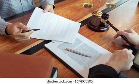 Rechtsanwältin, die mit dem Klienten über Vertragsunterlagen mit Messing-Skala über die Rechtsgesetzgebung im Gerichtssaal diskutiert, Beratung, um ihren Kunden zu helfen