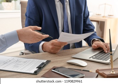 Lawyer working with client at table in office, focus on hands