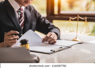 lawyer working on wooden desk with gavel and soundblock of justice law