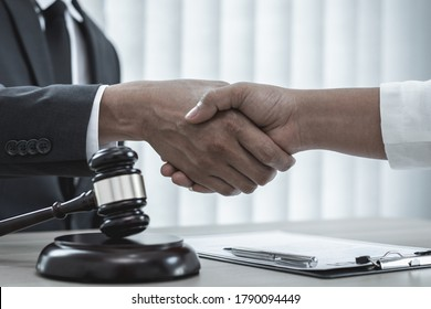 Lawyers or counselors shake hands with clients to congratulate the end of the case by the company, Negotiation or settlement of lawsuits concept.