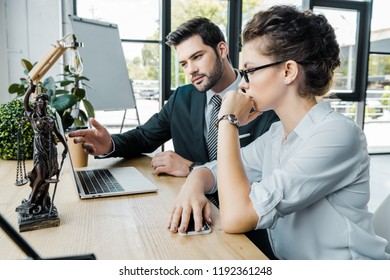 lawyers discussign work at workplace with laptop and femida in office