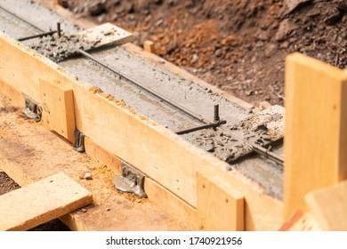 Lay of the cement or concrete into the foundation formwork with automatic pump. Building house foundation
