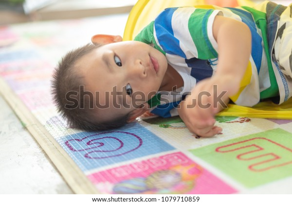 Lay down on the ground, focus on boy's face. Adorable little Asian boy happy to play with colorful tunnel.