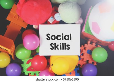 A lay flat happiness toys concept image of bunch of a mix child kids colorful ball toys fluffy kids puzzle foams a yellow rubber duck and a white canvas with a word SOCIAL SKILLS