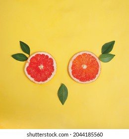 Lay flat owl face made out of fresh green leaves and sliced pink grapefruit on a bright yellow background - Shutterstock ID 2044185560