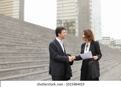 Layer and client standing on big gray stairs. Woman hold documents about court statement in hand. Man tell about very good end of litigation, and bouth smiling look really happy. Concept of pos