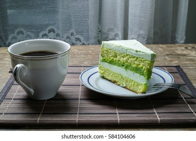 layer Pandan Cake  with a hot coffee on a wooden table.