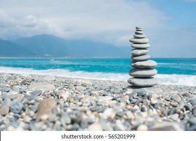 Layer of stone balancing at blue ocean beach.
