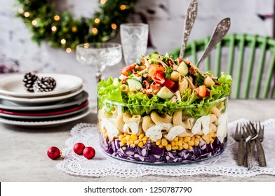 Layered Christmas Pasta Salad with Red Cabbage, Corn, Tomato, Cucumber, Cheese, Bacon and Herbs