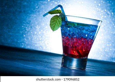 Layered cocktail with blue and red at the club