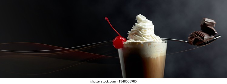 Layered coffee cocktail with whipped cream, cherry and pieces of chocolate. Conceptual image of the theme of dessert. Copy space.