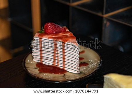 Layered Crepe Cake Drizzled with Syrup and a Fresh Fruit Strawberry