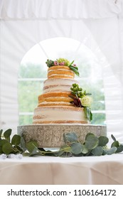 Layered delicious wedding cake decorated with floral pieces inside white tent venue.