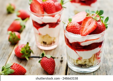 layered dessert with strawberries, biscuit cake and cream cheese on a dark wood background. tinting. selective focus
