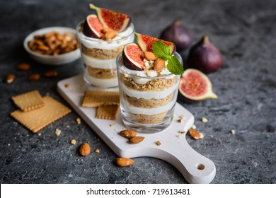 Layered mascarpone dessert with crushed vanilla biscuits, figs and almonds in a glass jar