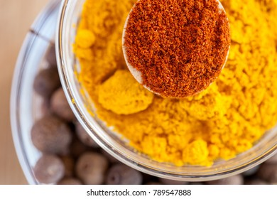 Layered paprika, turmeric and allspice in glass bowls on wooden surface, top shot