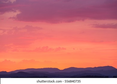 Layered purple hills ground a stunning rich pastel sky with low contrast clouds