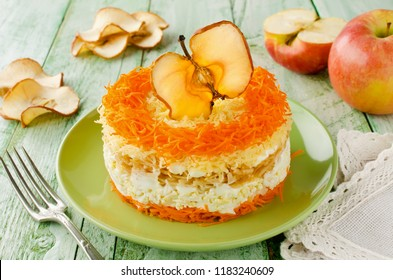 Layered salad with carrots, egg, cheese and apple. The salad is decorated with apple chip