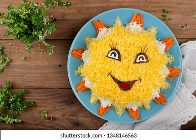 Layered salad in the form of Sun. Decoration is made of eggs and carrots