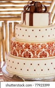 Layered white wedding cake with chocolate detail on silver serving dish