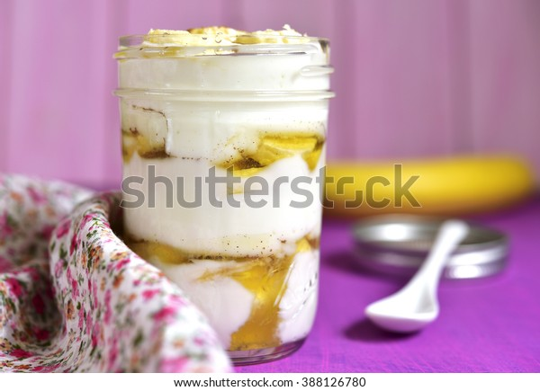 Layered yogurt dessert with banana and honey in a mason jar.