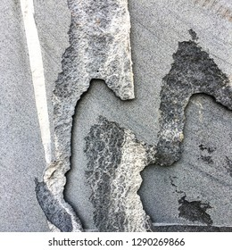 Layers of black roc or untreated granite slabs. Abstract shapes of unpolished and rough cut edges of granite or rock.