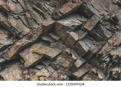 Layers and cracks in sedimentary rock on cliff face, background. Cliff of rock mountain. Rock slate in the mountain. Cracks and layers of sandstone.