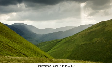 Layers of mountain peaks fade into the summer evening haze at Newlands Hause mountain pass above Buttermere in England's Lake District National Park.