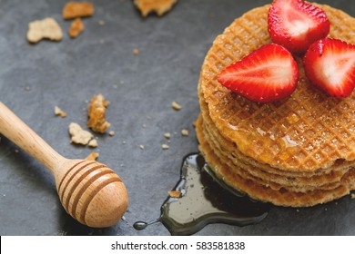 A layers of stroopwafel with strawberry, honey on top, honey stick stick on black slate stone, baked dough with a caramel - syrup filling in the middle, traditional snack from the Netherlands