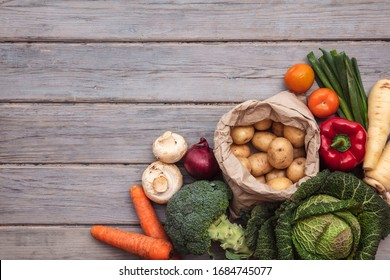 Layflat composition of fresh vegetables arranged on a wooden background