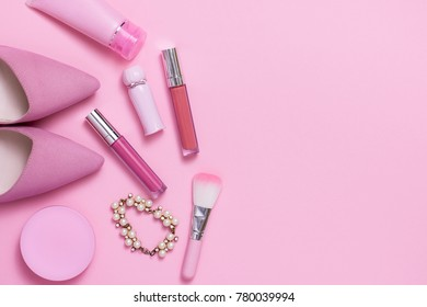 Layflat image of pink womans fashion and cosmetics products.