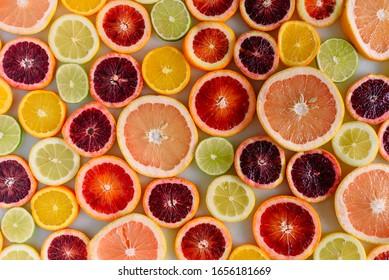 Vue à plat de divers agrumes dont des oranges sanguines, des pamplemousses, des citrons, des citrons et des mandarines sur une dalle de marbre