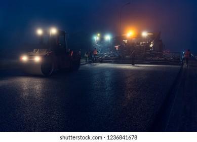 Nachts Asphaltfertiger mit Scheinwerfern. Straßenbau.