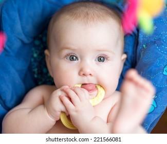 laying baby girl using teether
