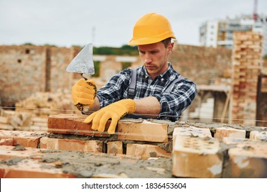 Laying bricks. Construction worker in uniform and safety equipment have job on building.