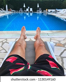 Laying by a pool mans legs POV reflections in a pool