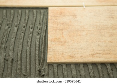 Laying ceramic tiles on a special cement grout. Selective focus. Shallow depth of field.