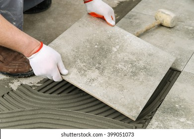 Laying Ceramic Tiles. Worker placing ceramic floor tile in position over adhesive.