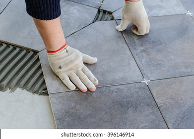 Laying Ceramic Tiles. Worker putting tiles on the balcony.
