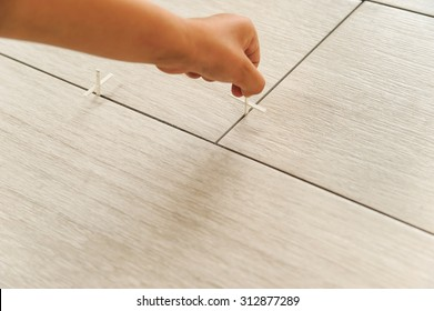 Laying Ceramic Tiles. Workers hand sets, plastic crosses between the tiles