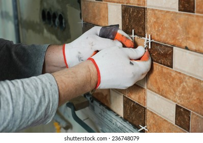 Laying Ceramic Tiles.Tiler aligns  seam between the tiles